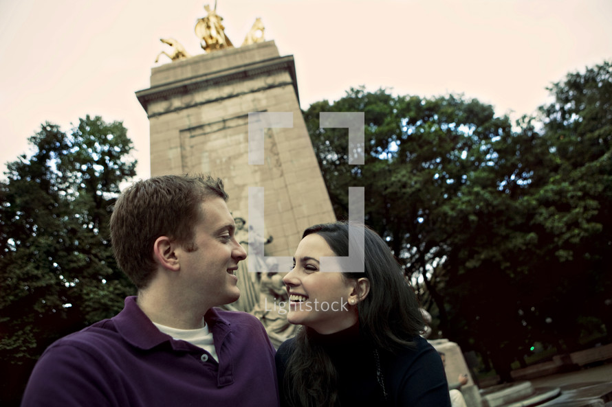 Couple sitting in front of a monument smiling