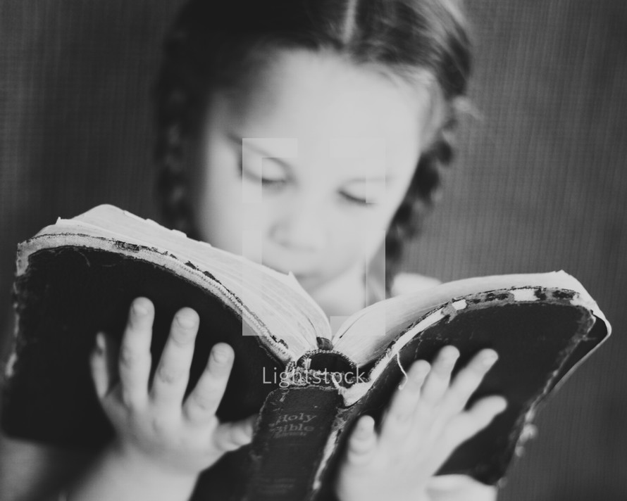 Little girl reading the bible