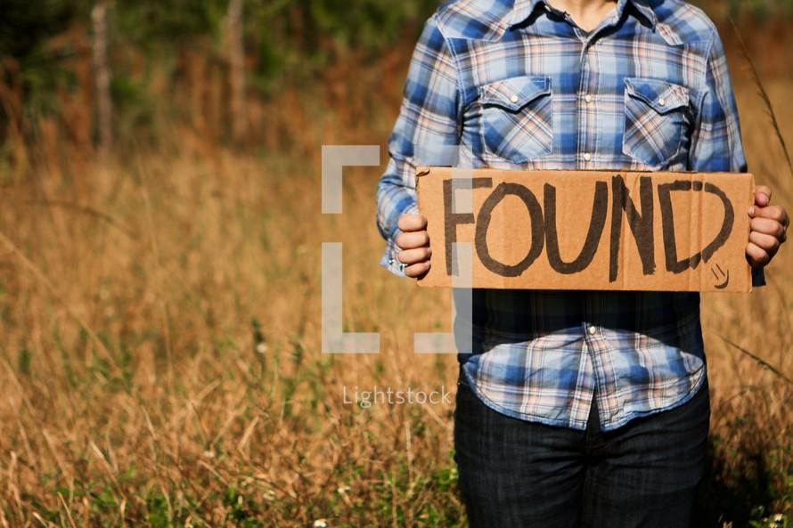 "Man holding ""Found"" cardboard sign"