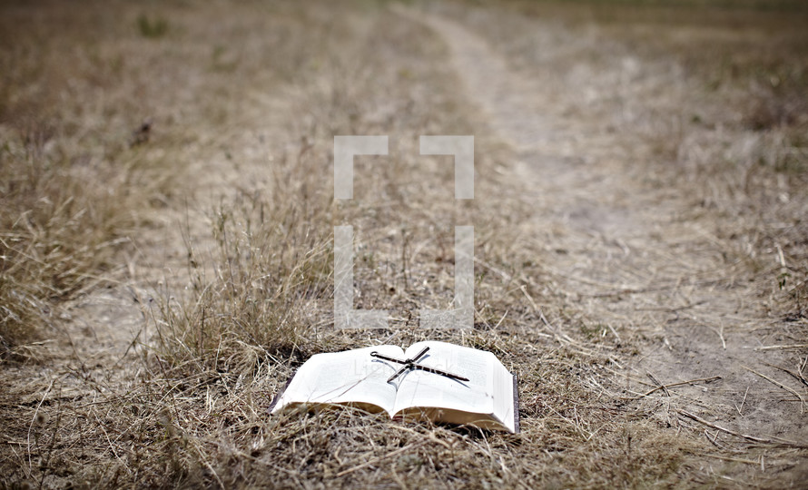 A Bible sets in the middle of a path - A cross made out of nails rests on top of the Bible