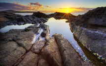A sunset over a tide pool.