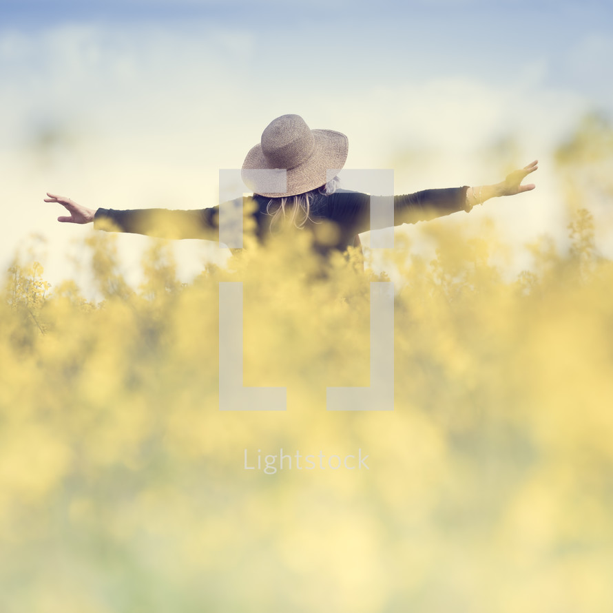 woman standing in a field with outstretched arms