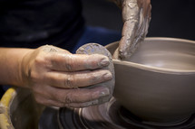 shaping clay on a potters wheel