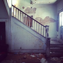 Staircase with wooden bainster in abandoned house with trash on floor.