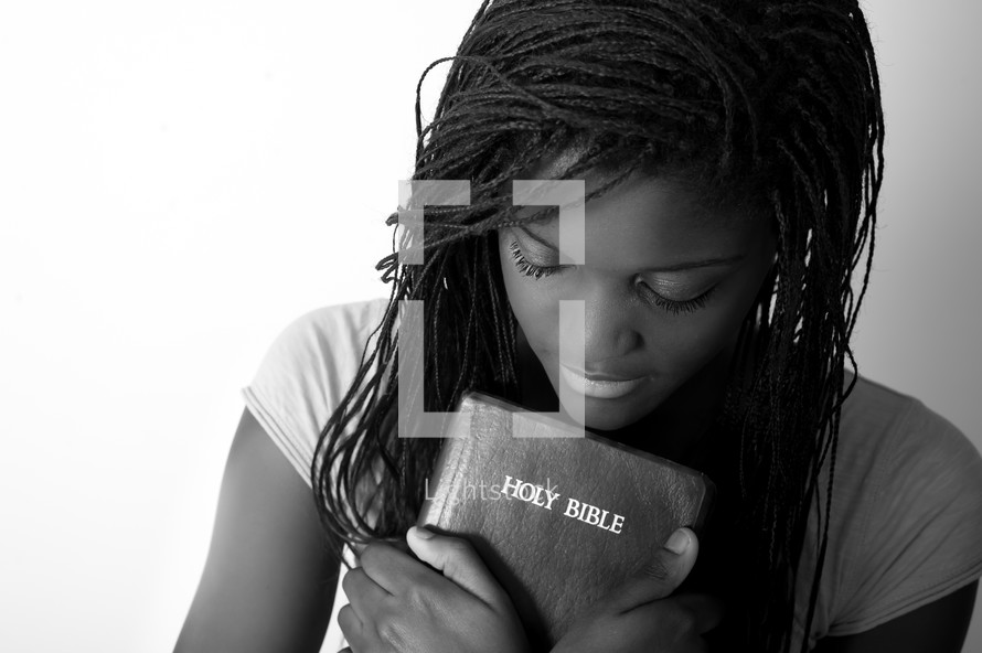 A teen girl holding a Bible.