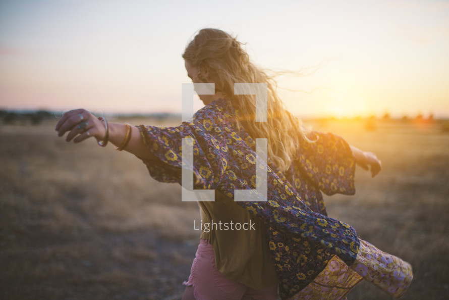 woman with outstretched arms alone in a field