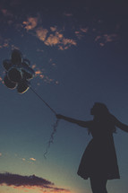 A silhouette of a woman holding balloons