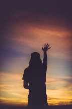 silhouette of a woman with hand raised
