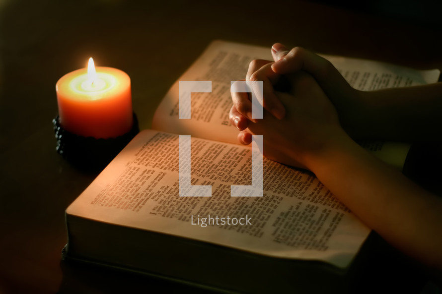 praying hands over the pages of a Bible and candlelight