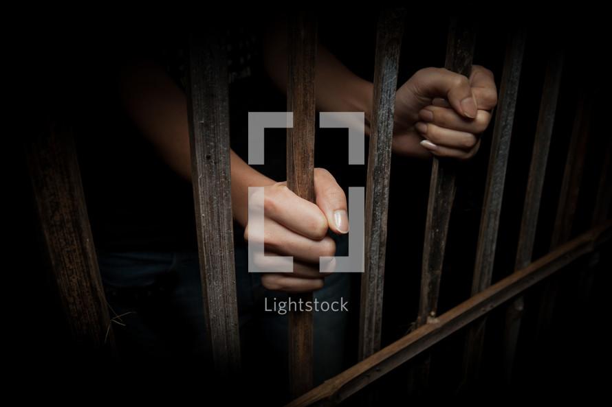 hands grabbing onto to jail bars