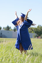 a student dances with joy on graduation day outside her school