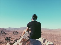 man sitting on a rock looking out at a desert