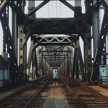 man standing between two sets of railroad tracks