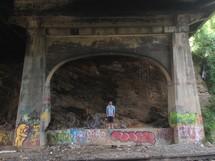 Man standing under a graffiti covered bridge,