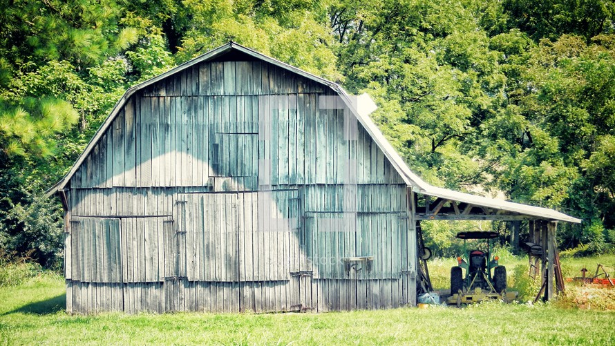 Wooden barn in a tree-lined pasture.