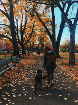 a woman walking her dog in the park in fall