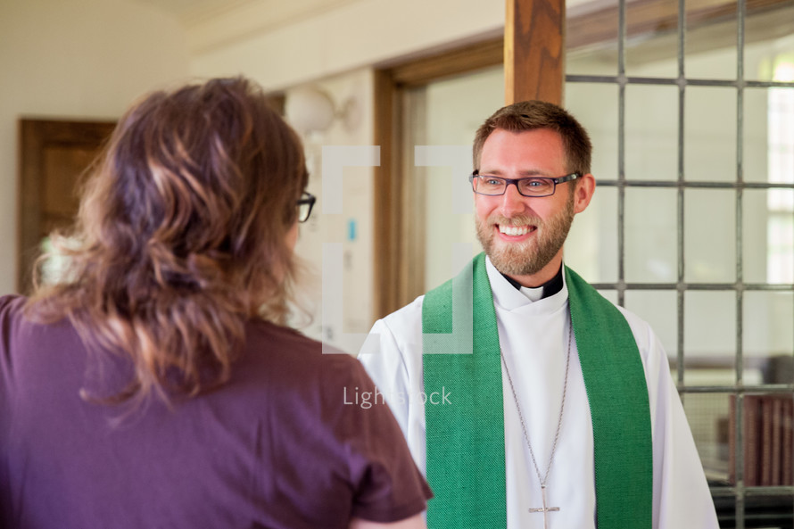 priest greeting a woman with a handshake