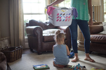 a mother holding a laundry basket with her daughter playing with toys on the floor