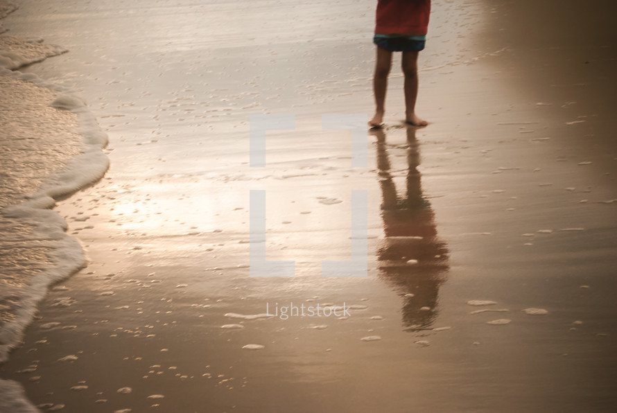 Wading child reflected in the water.