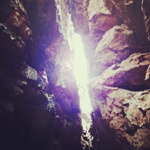 Light beaming through two rocky cliffs.
