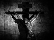 A black & white (b&w) crucifix, statue of Jesus, wrapped in a shawl against a stone brick wall.