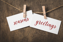words season's greetings on white card stock hanging from a clothespin on a clothesline