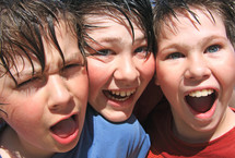 a group of 3 very happy young friends after a water fight