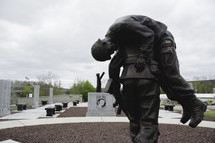 soldier carrying a fallen soldier statue at a memorial