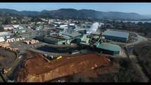 Aerial Video Flying Over Lumber Mill and Coastal Town