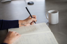 businesswoman writing in a notebook at a meeting