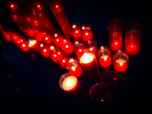 An out-of-focus shot of many red church candles.