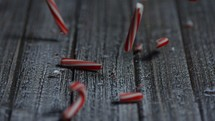 Candy canes falling onto a wooden table and smashing in slow motion
