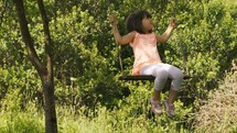 a little girl on a rope swing