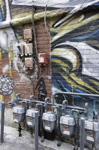 utility boxes and gas meters and graffiti on a wall