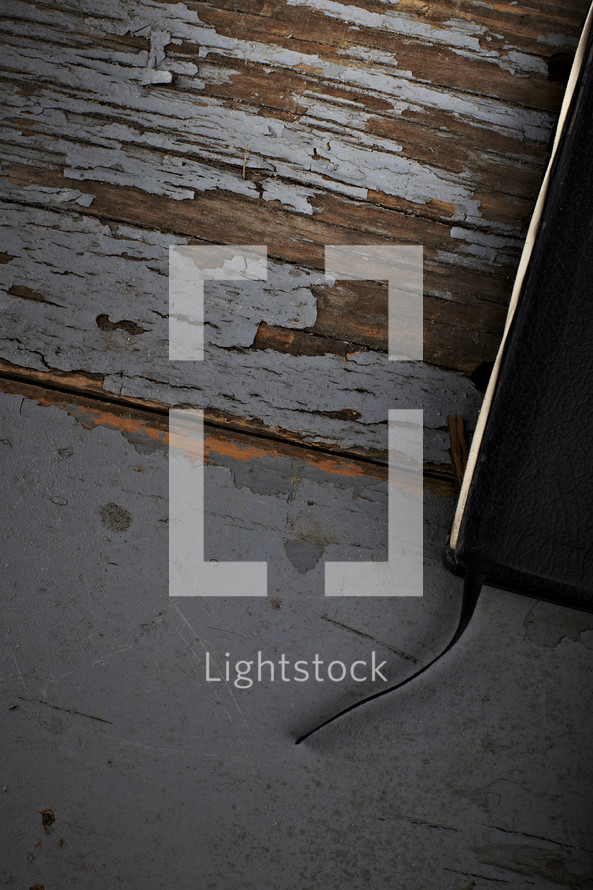 The edge of a Bible and bookmark - sitting on a wooden table