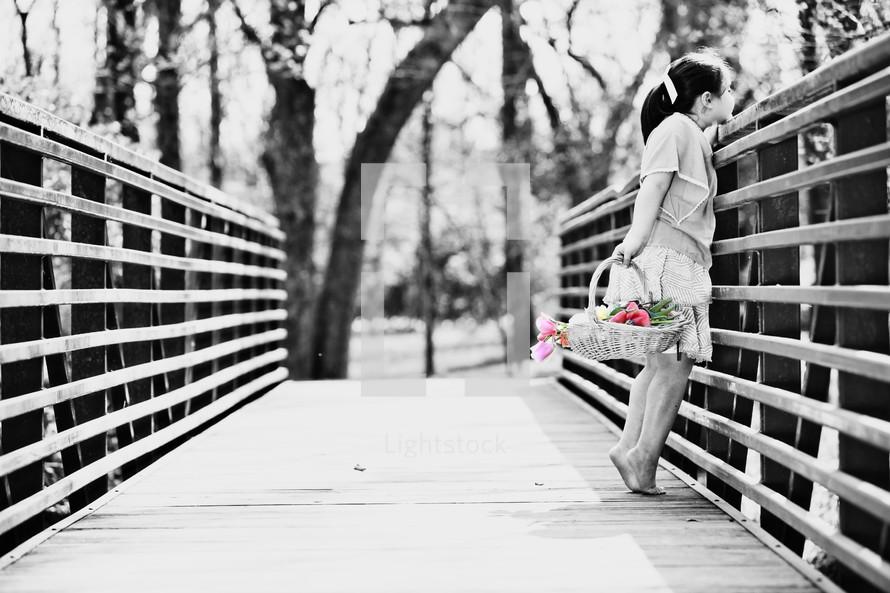 Girl carrying basket of flowers across wooden bridge.