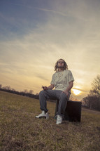 young man with dreads sitting outdoors