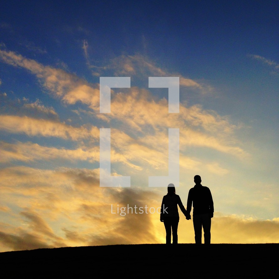 silhouette of a man and woman holding hands