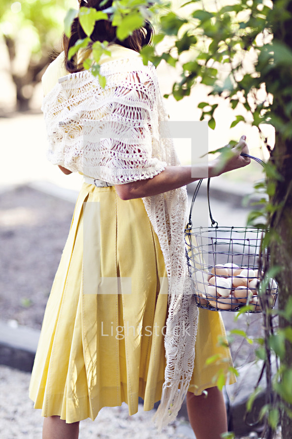 A woman  carrying a basket of eggs in yellow dress summer spring