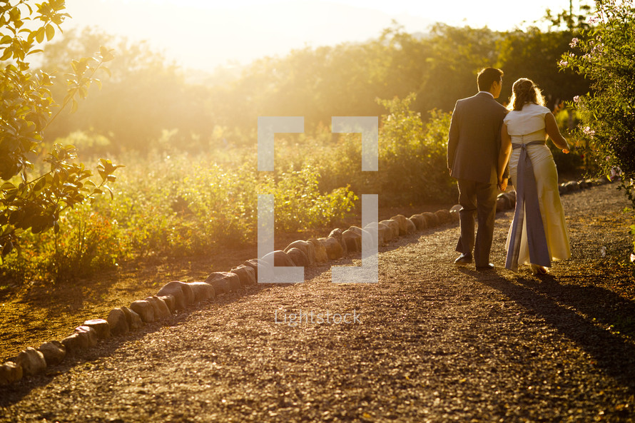 bride and groom walking down a dirt road holding hands fall at sunset. Man wife