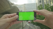 Personal perspective of a businessman holding a smartphone with a green screen