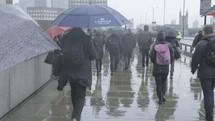 Commuters walking in the rain at rush hour on London Bridge, London