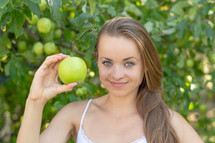 a young woman holding up a green apple
