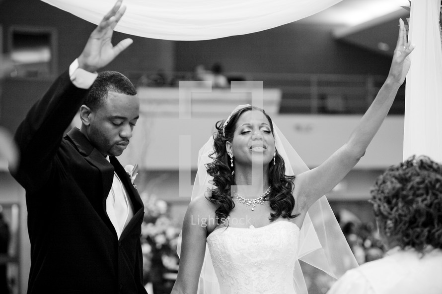 bride and groom with hands raised in praise and worship to the Lord