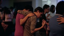 people arms around each other during a worship service