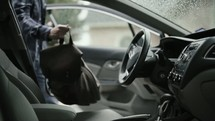 a man throwing his bag in a car and driving