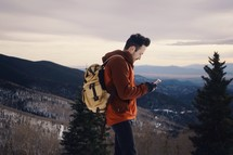 a hiker walking downhill with a gps