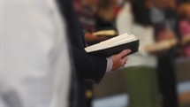 people singing from hymnals