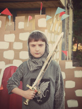 a boy holding a sword standing in front of a cardboard castle