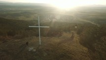 man praying next to a cross on a mountaintop